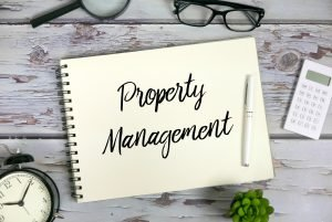 Top view of magnifying glasses,sunglasses,calculator,plant,clock,pen and notebook written with Property Management.